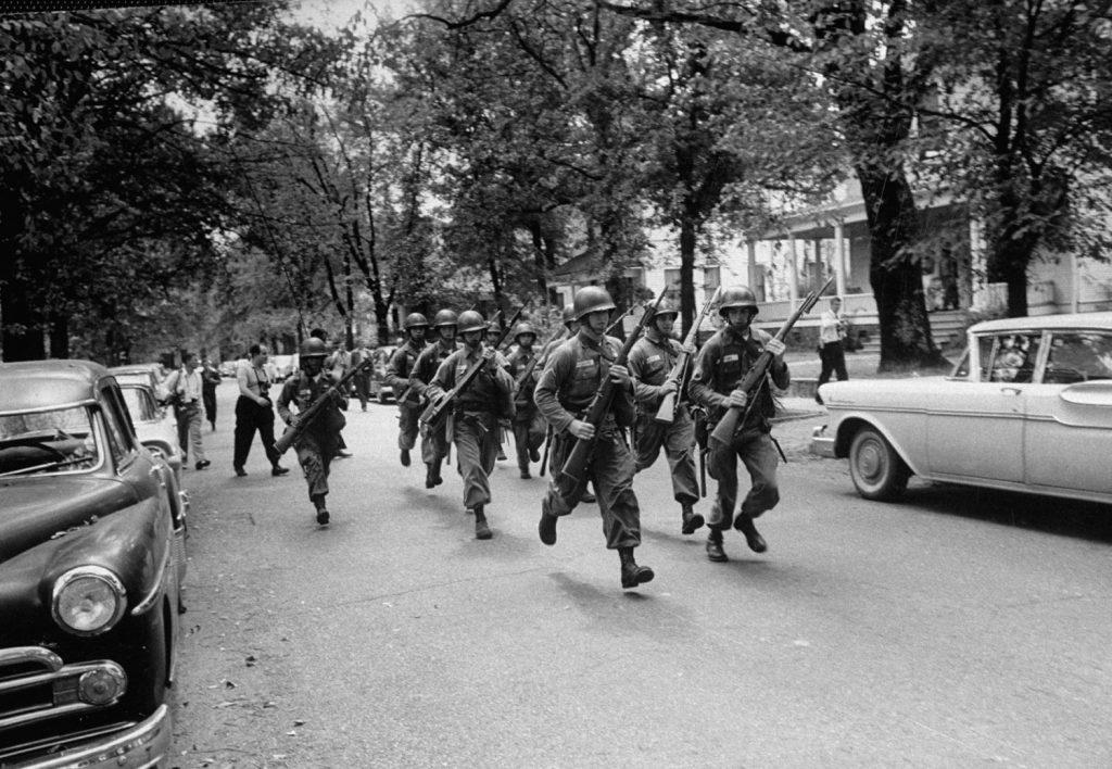 Troops race to break up a crowd protesting school integration, Little Rock, Arkansas, 1957.