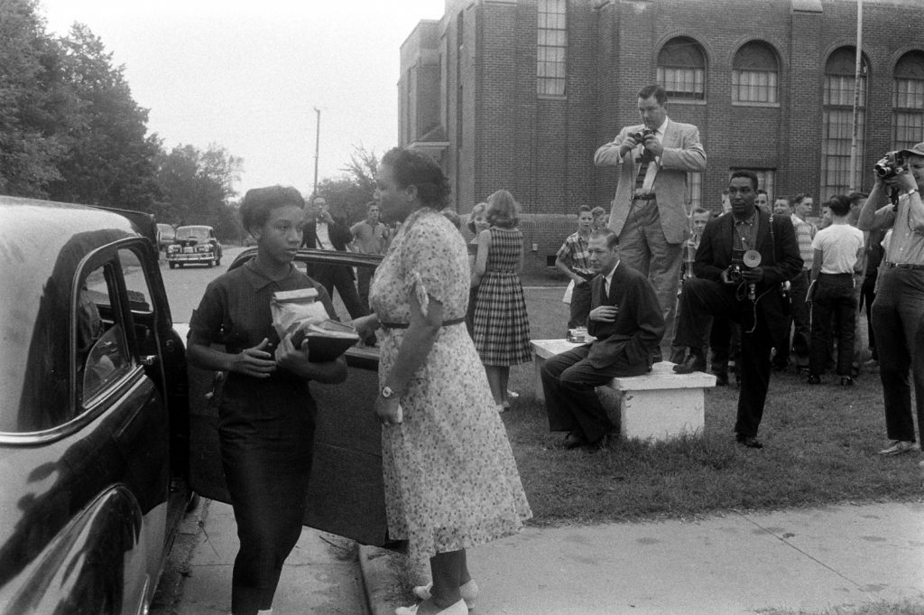 At a school in Van Buren, Arkansas, African-American students arrive in front of a crowd of journalists and other onlookers, 1957.