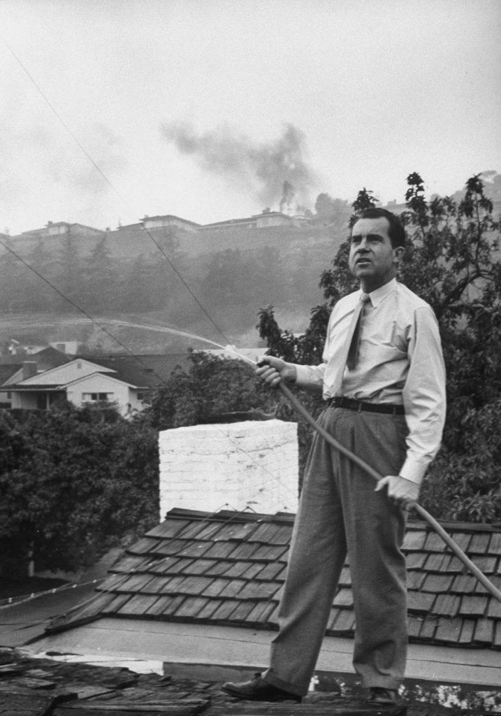 Senator Richard Nixon on the roof of his home in Los Angeles, trying to douse fires caused by a brush blaze, 1961.
