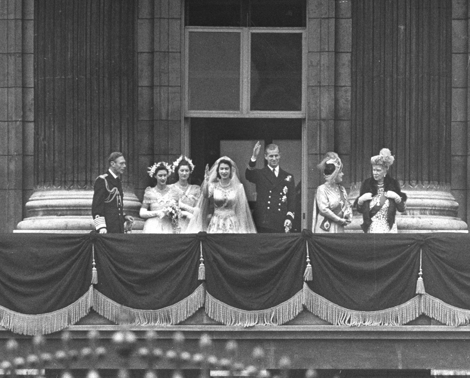 Royals on the balcony of Buckingham Palace: (l. to r.) King George VI, Princess Margaret Rose, unidentified, Princess Elizabeth, Prince Philip, Queen Elizabeth and Queen Mother Mary after wedding of Elizabeth and Philip.
