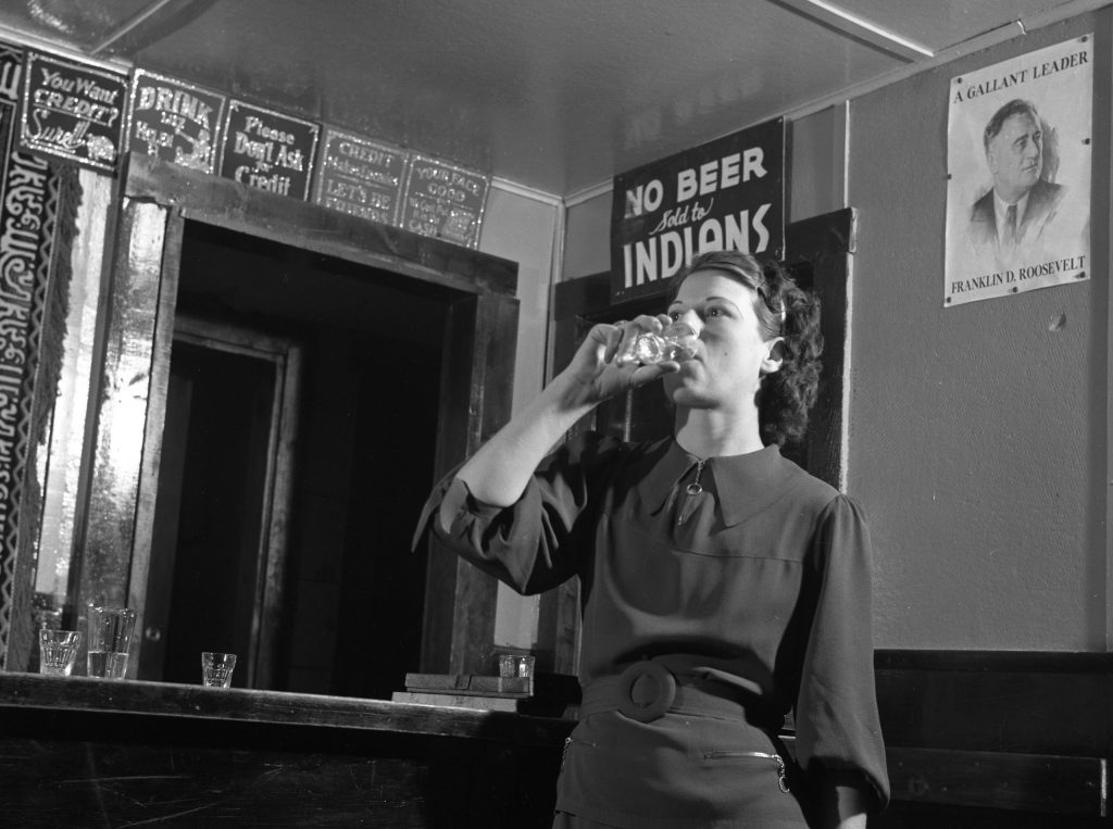 "Beneath a ""No Beer Sold to Indians"" sign, a woman tosses back a drink in Montana, 1936."
