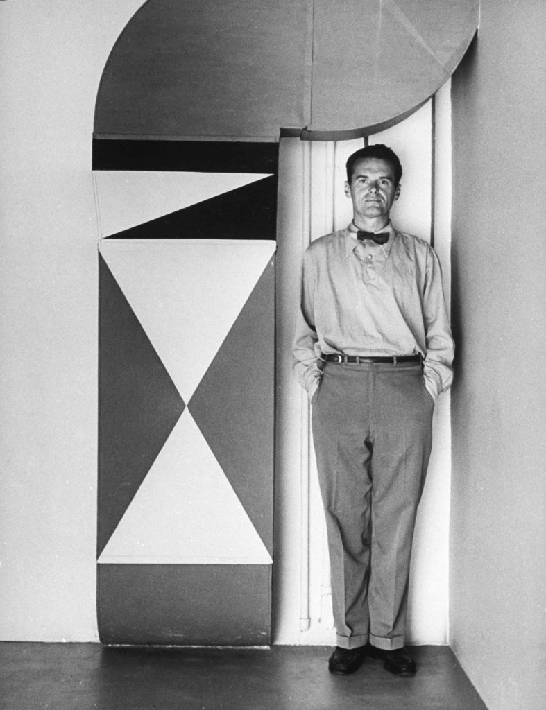 Charles Eames ... earnest, reticent, eternally bow-tied man of 43. Decoration on heating duct at left is a piece of Eames whimsy.