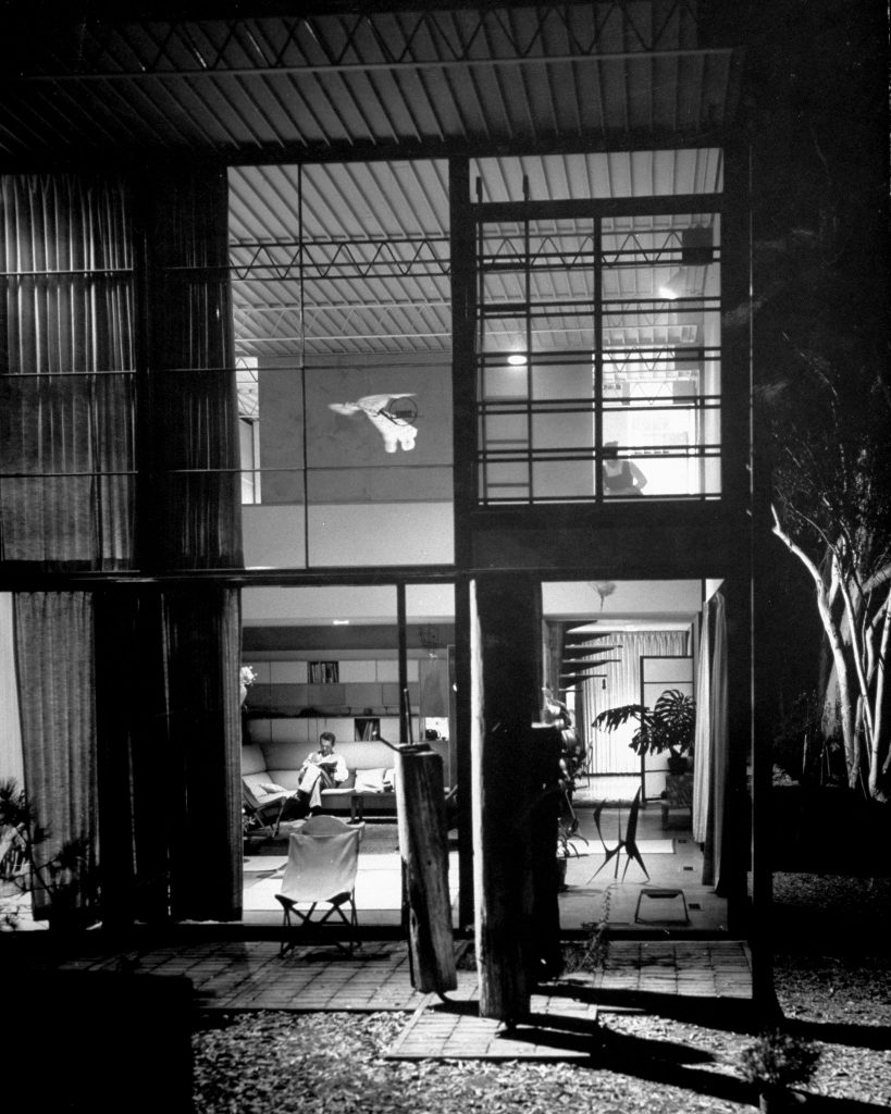 Interior view shows living room's 17-foot-high ceiling, unadorned steel-truss construction, to which Eames clamps lamps for varied lighting effects. He puts up the pilings from an old pier outside the door because he liked their looks. He similarly suspended a Chinese owl kite and toy French horn from the ceiling.