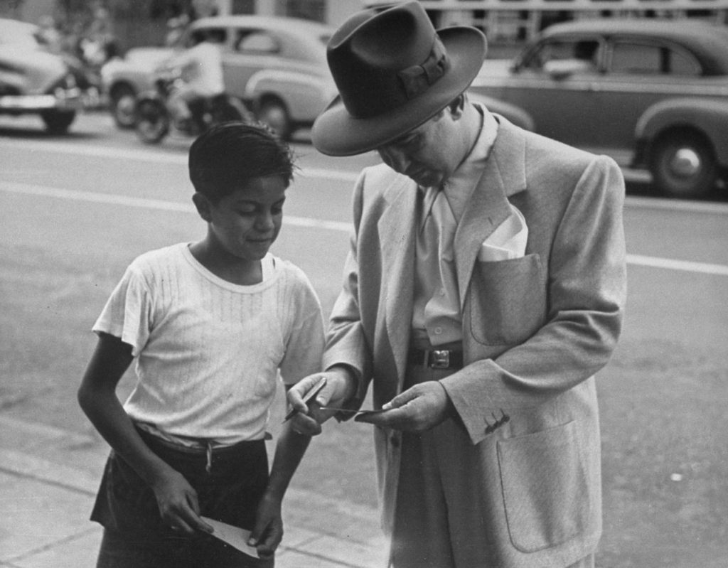 Mickey Cohen signs an autograph for a young fan, Los Angeles, 1949.