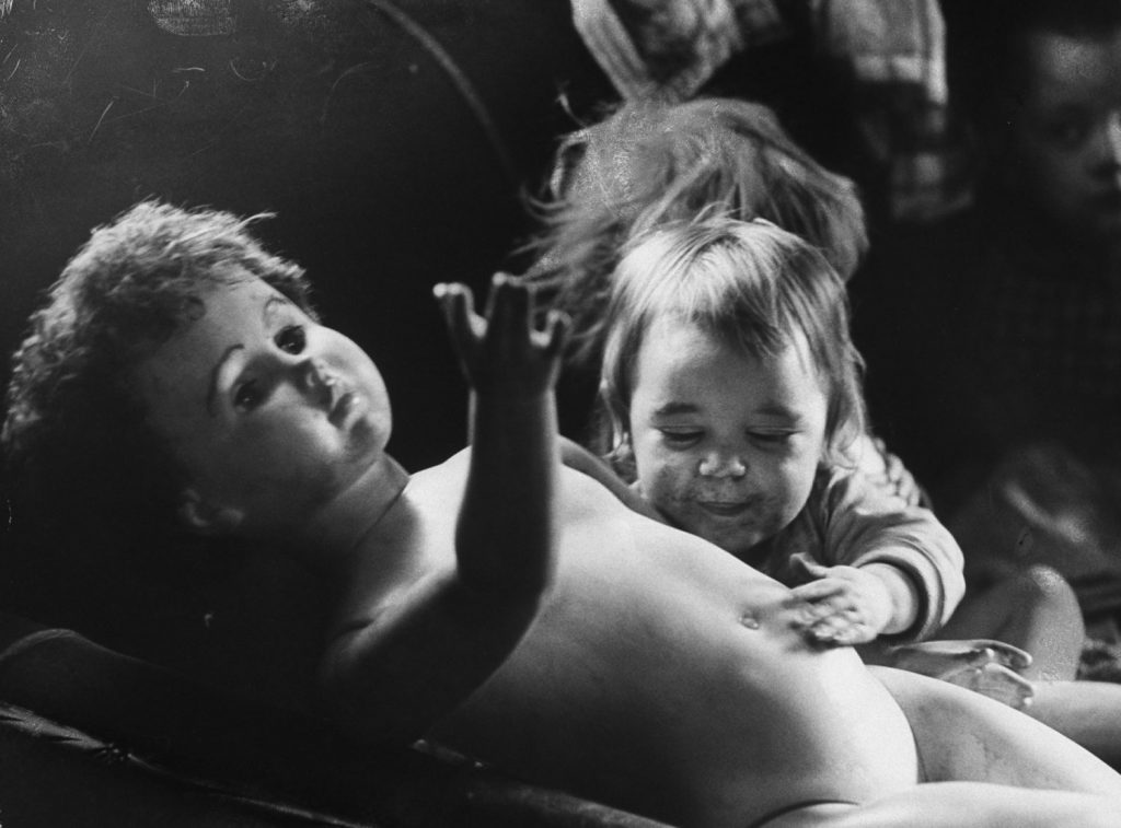 Nadine McFall, 1, happily reaches over to pat the stomach of a huge doll -- its wardrobe long since lost and never replaced -- as she squats on a crowded couch in her great grandmother's shack near Neon.