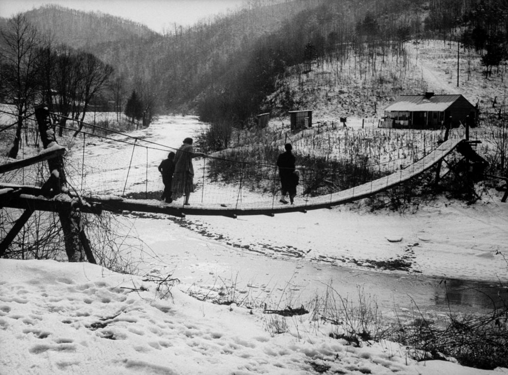On a wintry afternoon in Line Fork Creek a family trudges across a rickety suspension bridge over a sewage-polluted stream to its two-room shack.