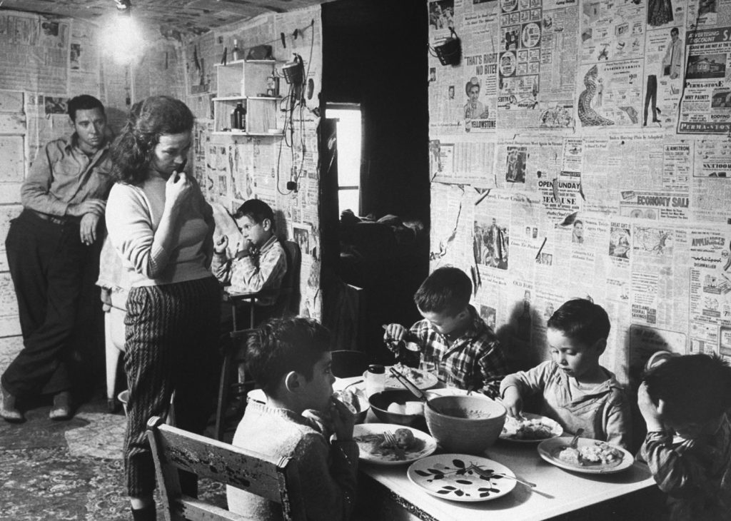 Youngsters lap up a surplus-commodity supper of pan-fried biscuits, gravy and potatoes at the Odell Smiths of Friday Branch Creek. The newspapers were pasted by Mrs. Smith in an effort to keep the place neat.