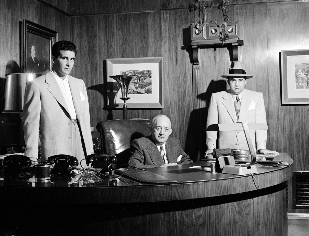 """Mickey Cohen's enforcer, """"Johnny Stomp"""" Stompanato (famously stabbed and killed by Lana Turner's 14-year-old daughter, Cheryl Crane, in 1958), business manager Mike Howard and Cohen pose in Cohen's office in Los Angeles, 1949."""