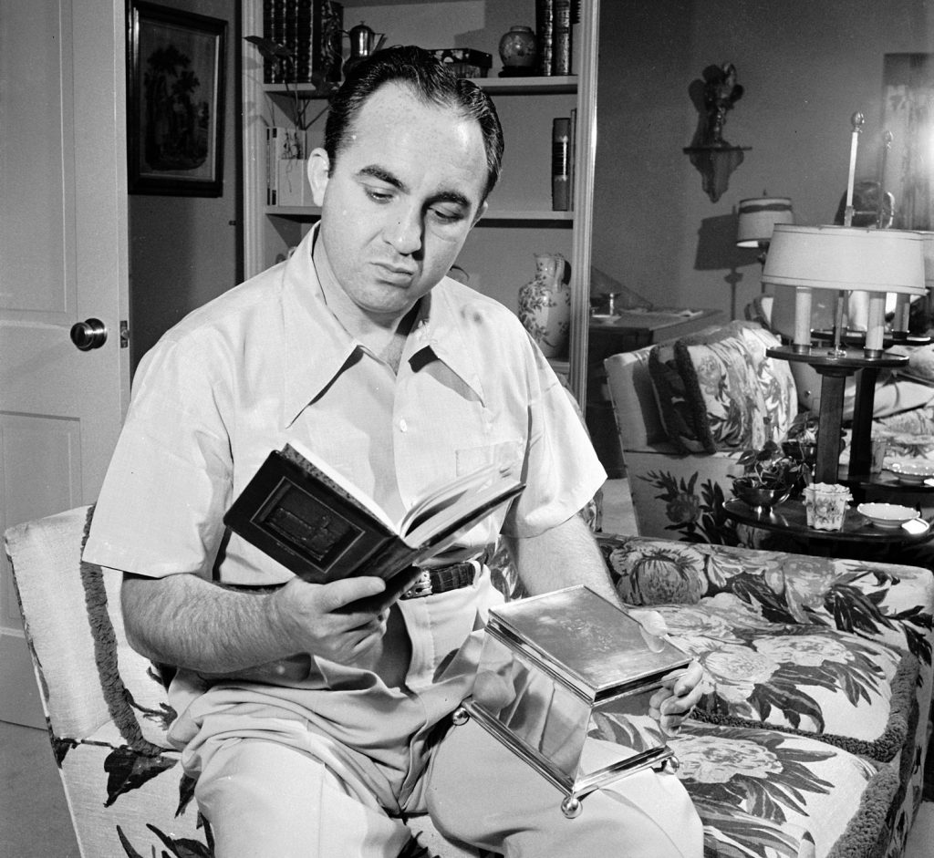Gangster Mickey Cohen at home with a book given to him by the Hebrew Committee of National Liberation, Los Angeles, 1949.