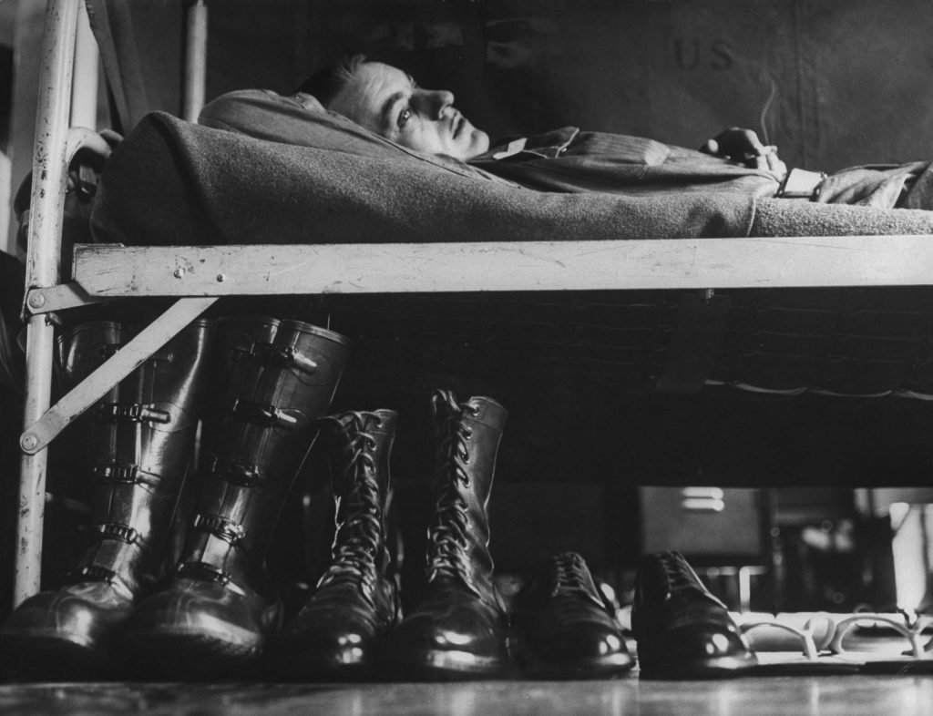 A draftee relaxes on his bunk during basic training, Fort Carson, Colorado, 1955.