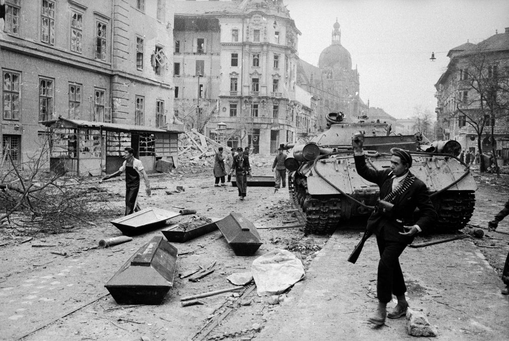 A disabled tank near coffins being used for the bodies of Russian soldiers killed during the popular uprising against the Communist-backed Hungarian government, Budapest, 1956.