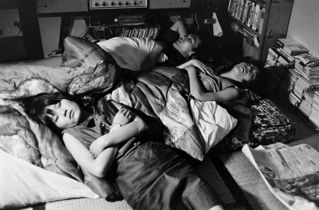 Yoko (left) ends a long night of clubbing by sleeping on a futon in a friend's room, Japan, 1964.