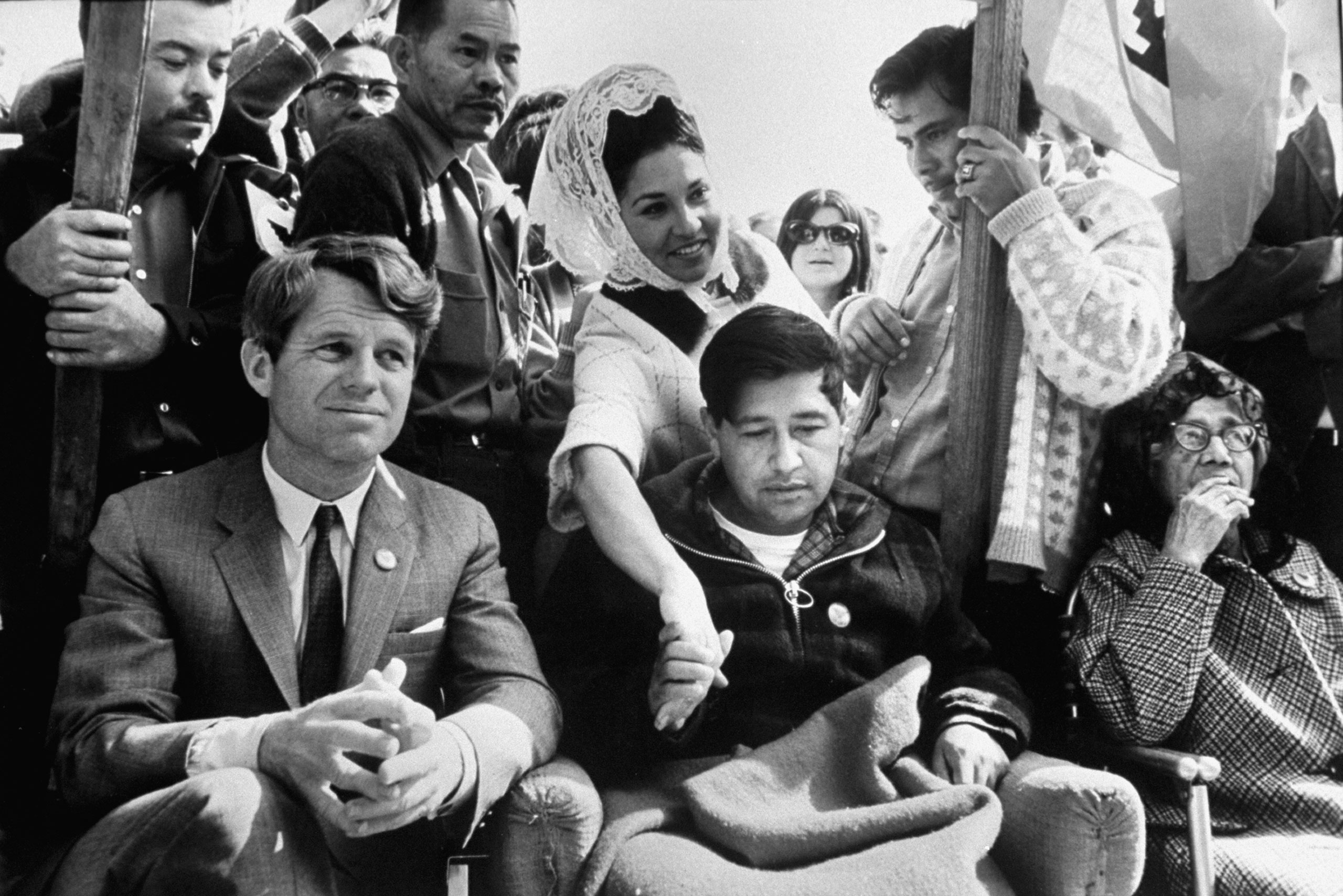 Robert F. Kennedy lends moral support to striking grape pickers and their leader, Cesar Chavez (on hunger strike), 1968.