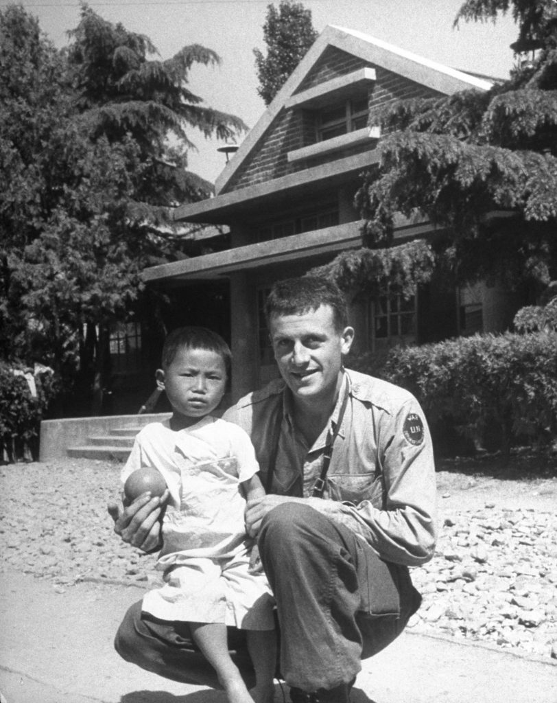 LIFE photographer Michael Rougier, kneeling on ground with a Korean orphan.