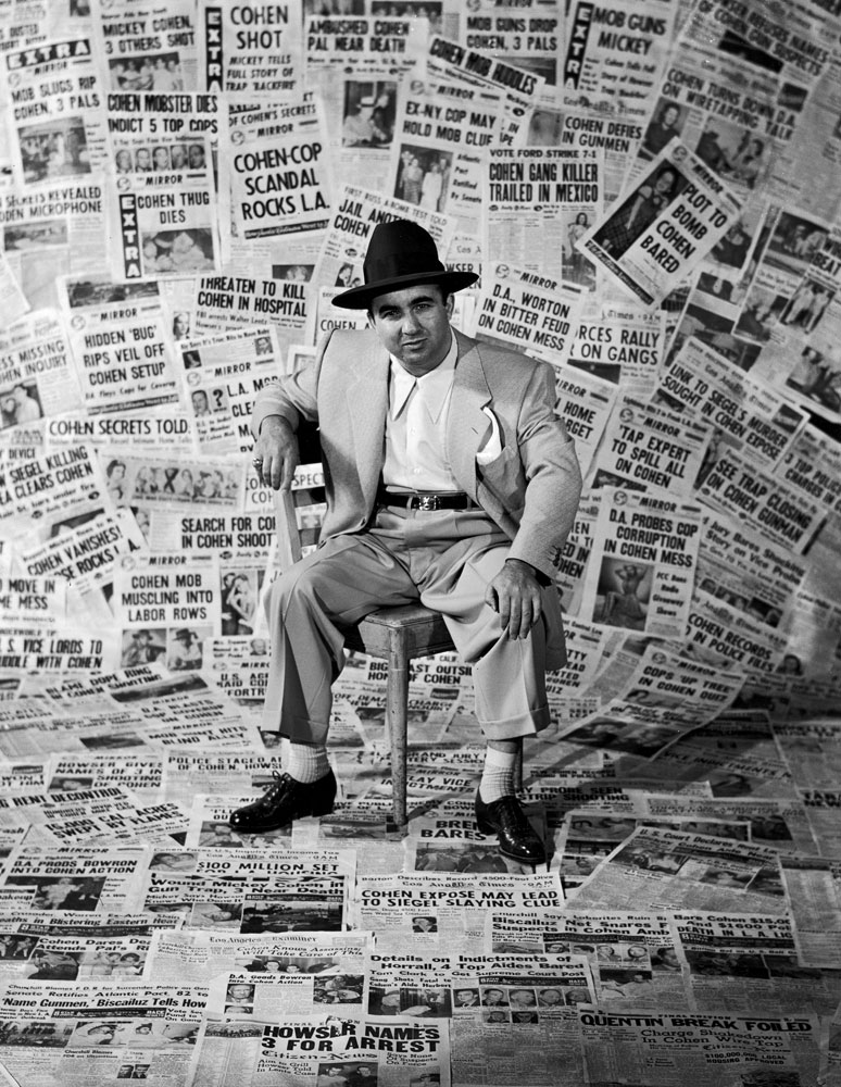 Gangster Mickey Cohen sits amid the front pages of newspapers that helped make him the city's' most infamous citizen, Los Angeles, 1949.