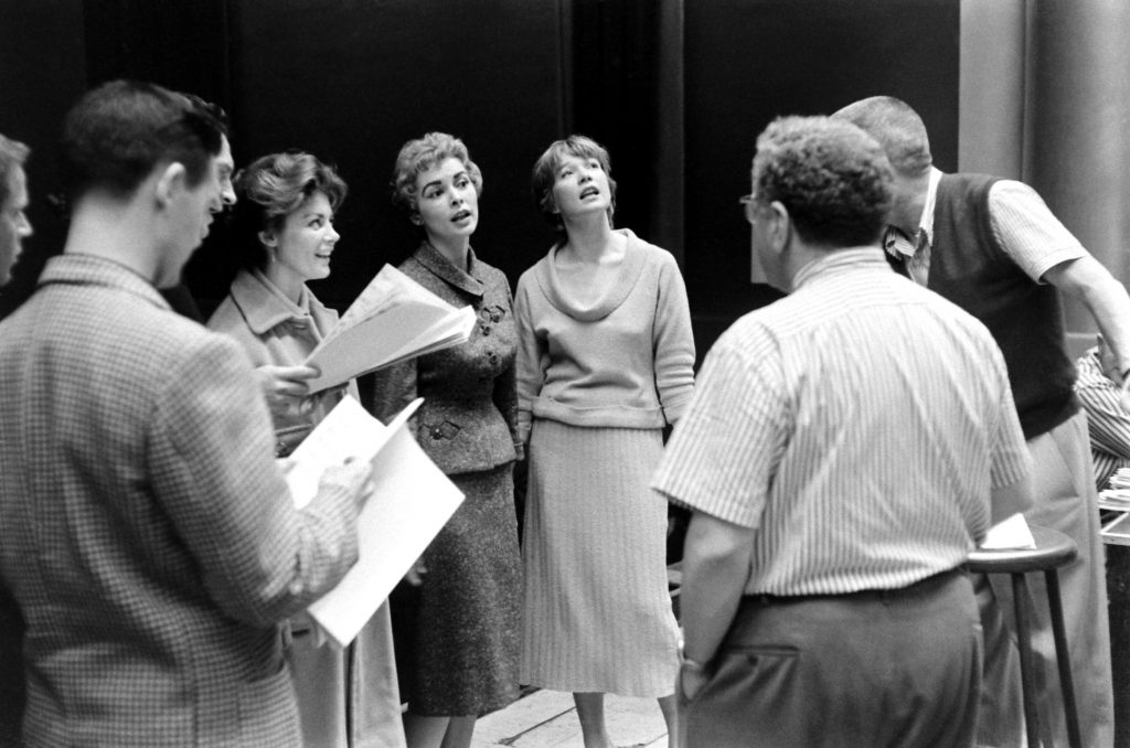 Inside Los Angeles' RKO Pantages theater, home of the Academy Awards from 1949 through 1959, Janet Leigh and Shirley MacLaine practice a tune.