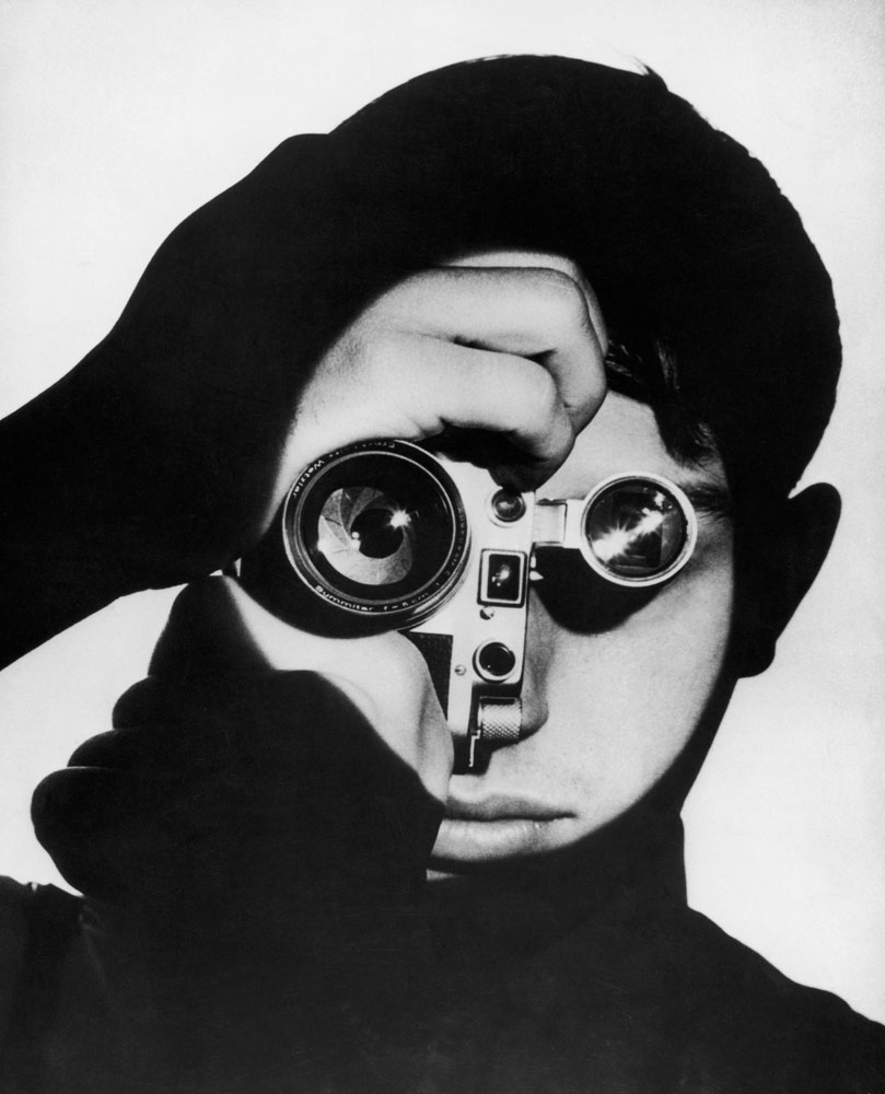 Photographer Dennis Stock holds a camera in front of his face, 1955.