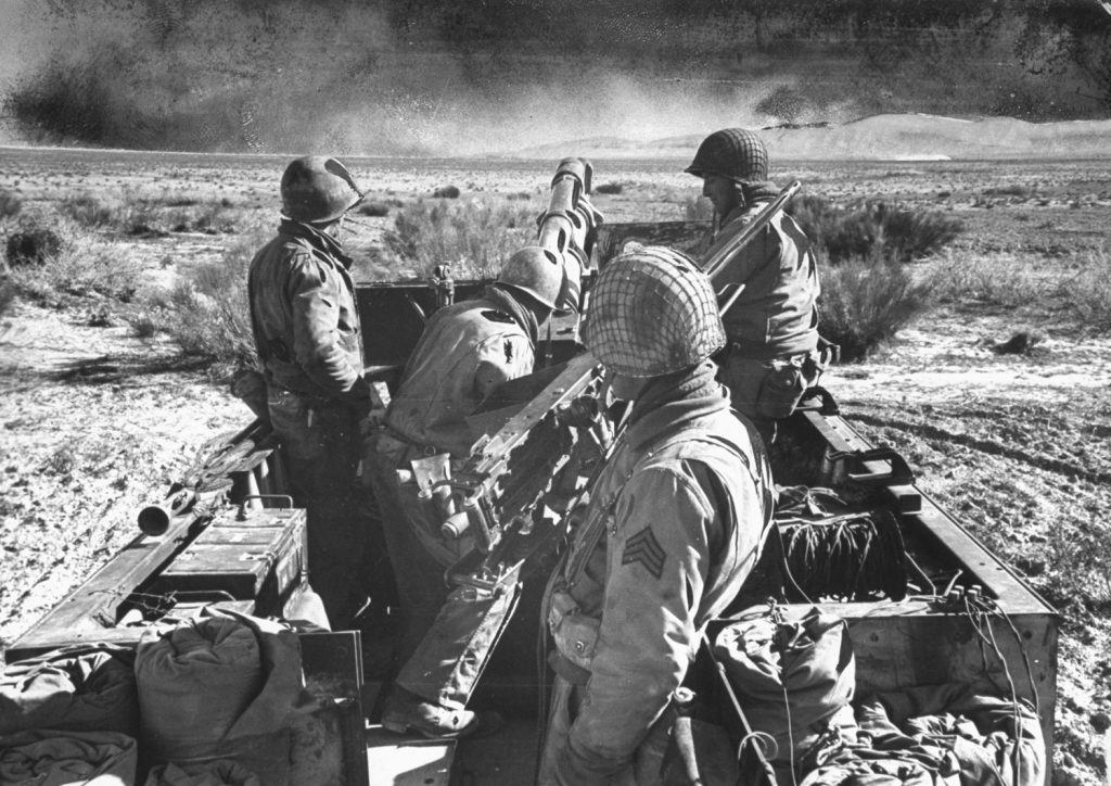 A tank-artillery team stands on alert. This kind of unit -- a 105mm. howitzer mounted on a half-track -- has proved a 'winning combination,' according to Army experts, in ground warfare in Tunisia.