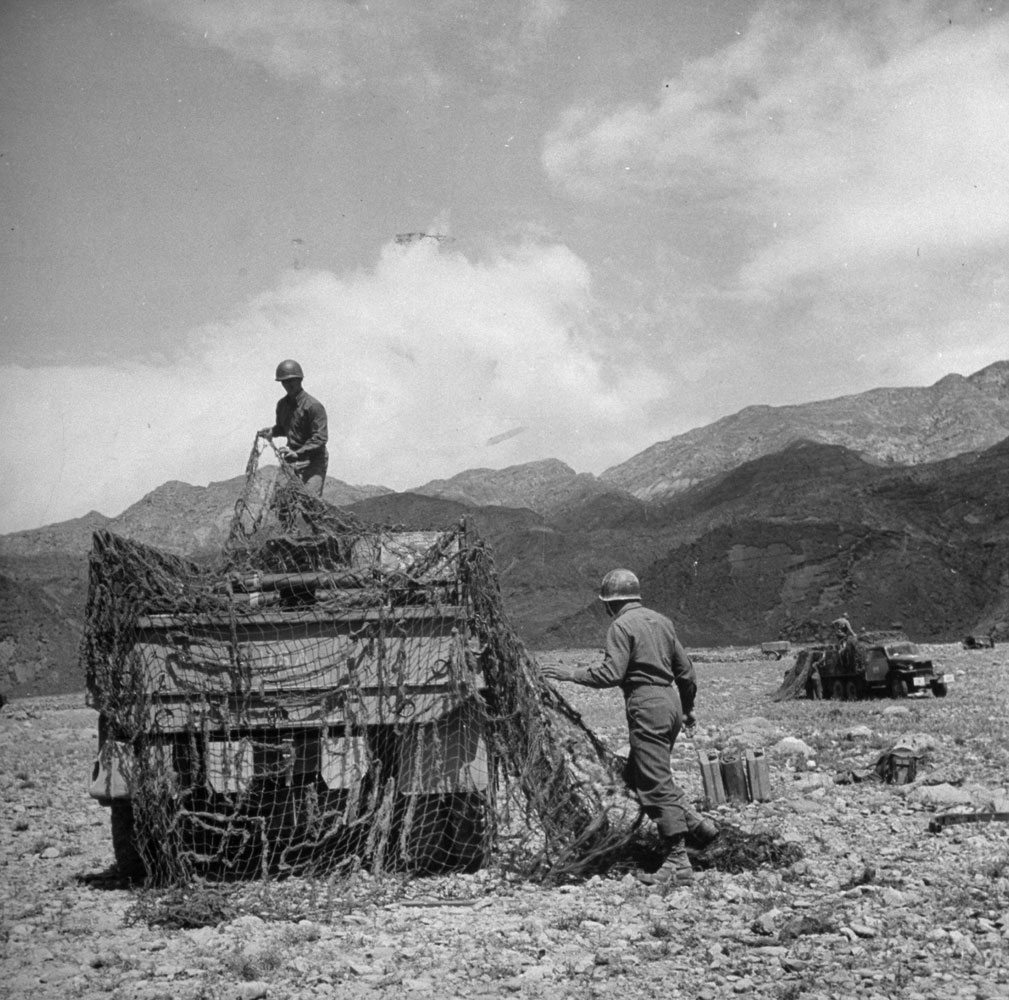 Covering two and a half ton truck with net after arrival at ammo dump near front. Ammo is moved to artillery at night. Ammo is 105mm in clover leaf (cluster of 3 shells).