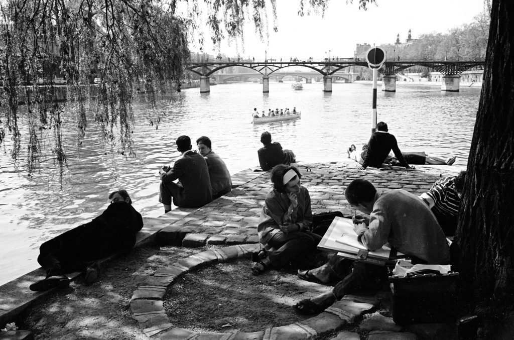 People enjoying an afternoon on the banks of the Seine River, 1963.