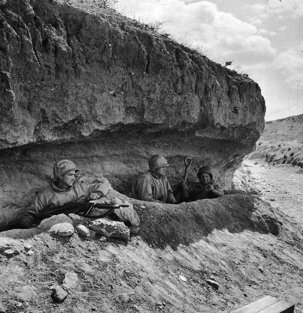 Three tank-destroyer men take refuge in foxholes under a bank during a Stuka bombing attack. U.S. tank destroyers, with 3-inch guns, played a big part in defeat of 10th Panzers, Tunisia, 1943.