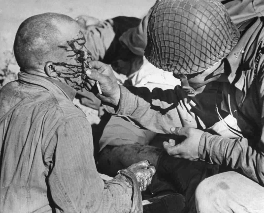 Bespattered with blood and oil after strafing attack by nine Me-109s [Messerschmitts] on first day of battle, a wounded half-track gunner vainly tries to swallow a sulfa tablet. Attending officer subsequently flushed it down his throat with water. Three other men on the half-track were killed.