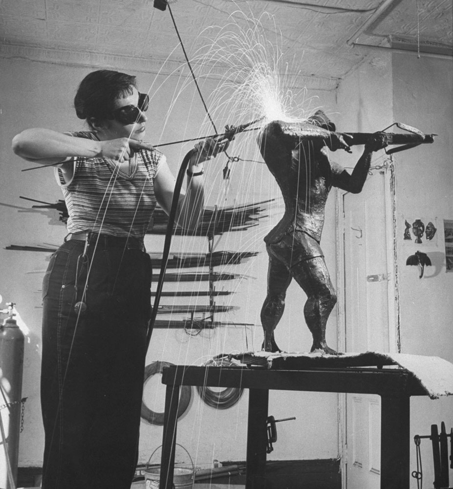Sculptress Ruth Vodicka alters the shoulder of her statue of William Tell, 1956. (She also used her tools to do welding repairs for neighbors.)