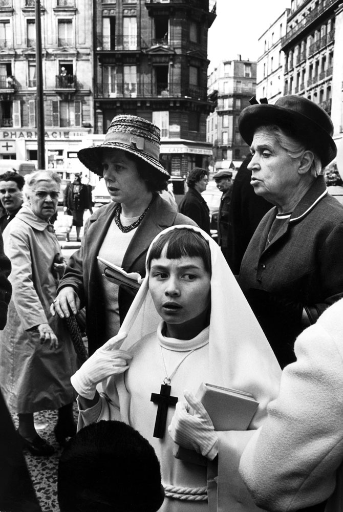 Parisian girl dressed for her first communion accompanied by family members, 1963.