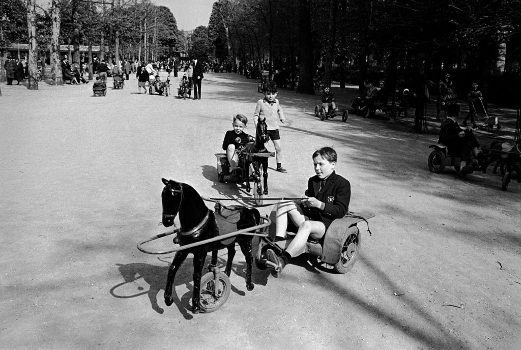 French children playing on toy horse and buggy vehicles, 1963.