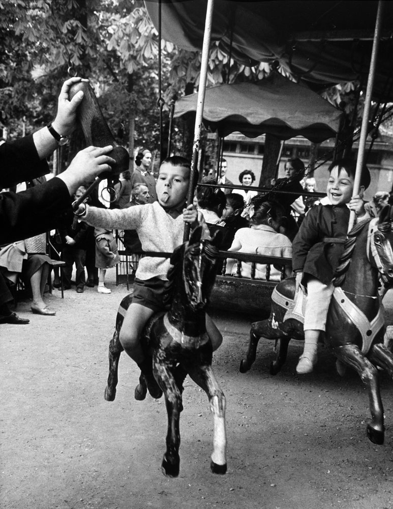 Little boy on merry-go-round at the Tuileries Gardens, sticking out his tongue, 1963.