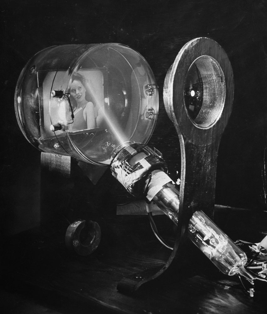 Laboratory scene of how television works, showing the image of a girl being focused through a lens onto a sensitive plate as an electron beam (its path shown by glowing gases) scans it, 1944.