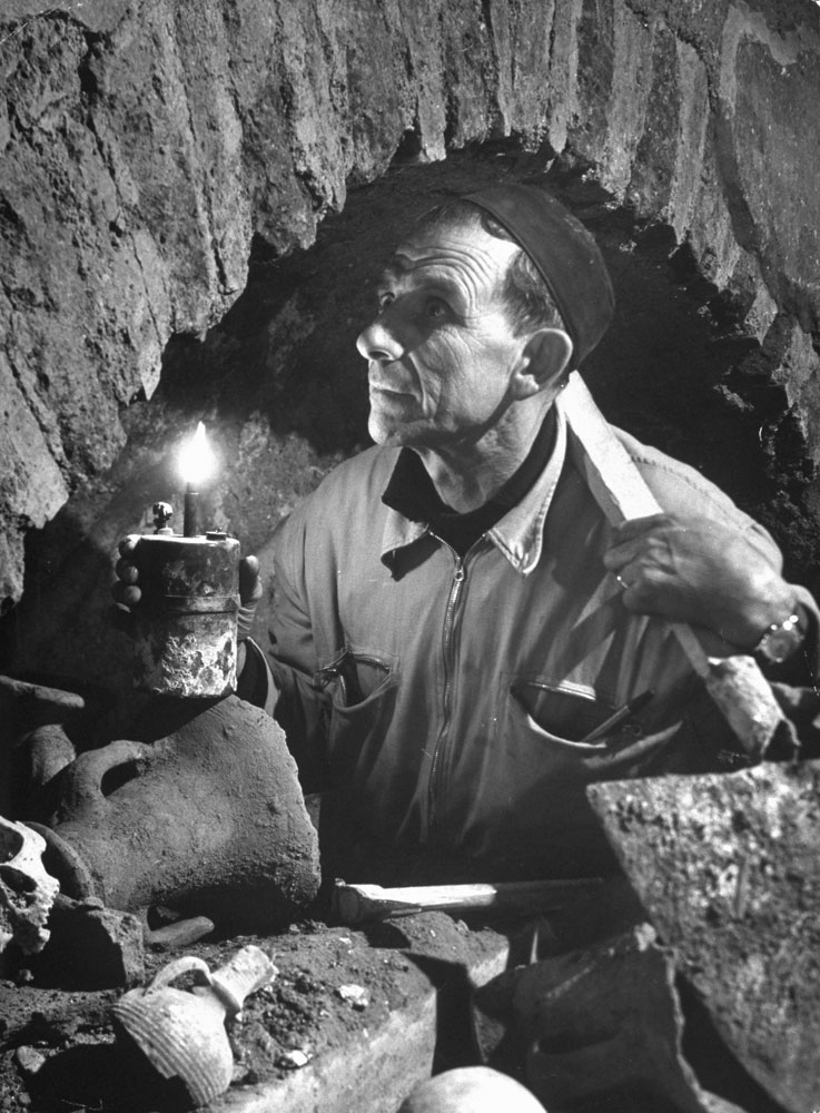 In a clutter of bones and artifacts the foreman of a team of Vatican workmen examines an ancient archway, St. Peter's, Rome, 1950.