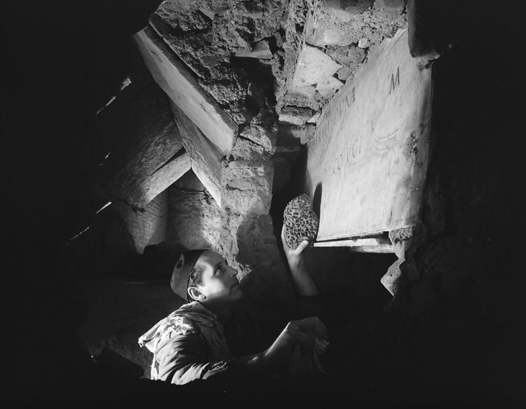A workman cleans an inscription during the excavation beneath St. Peter's in Rome, 1950.