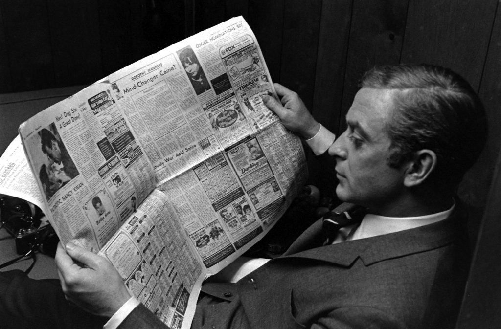 Michael Caine reads a paper, and an article about himself, in Los Angeles in 1966.