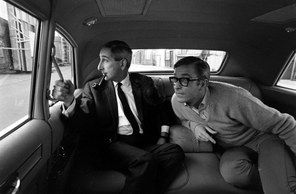 Michael Caine and an unidentified man in a car in Los Angeles in 1966.