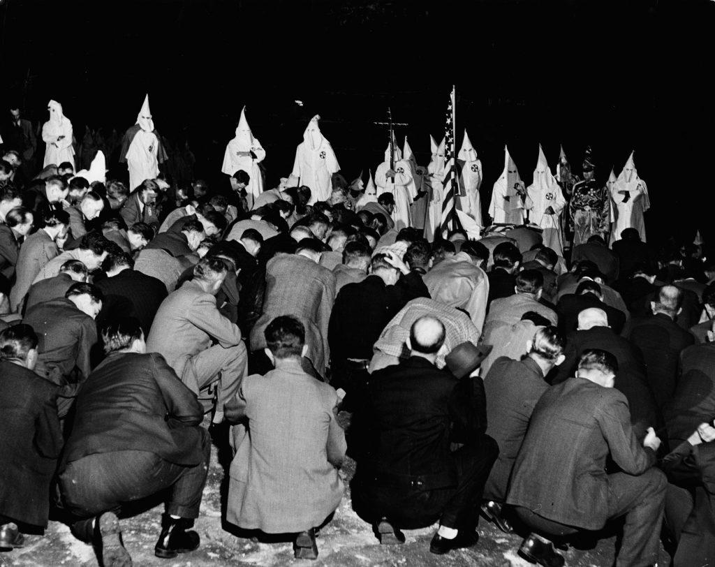 Klan initiates (including some Atlanta policemen) kneel before the local Grand Dragon during a ritual in Georgia, 1946.