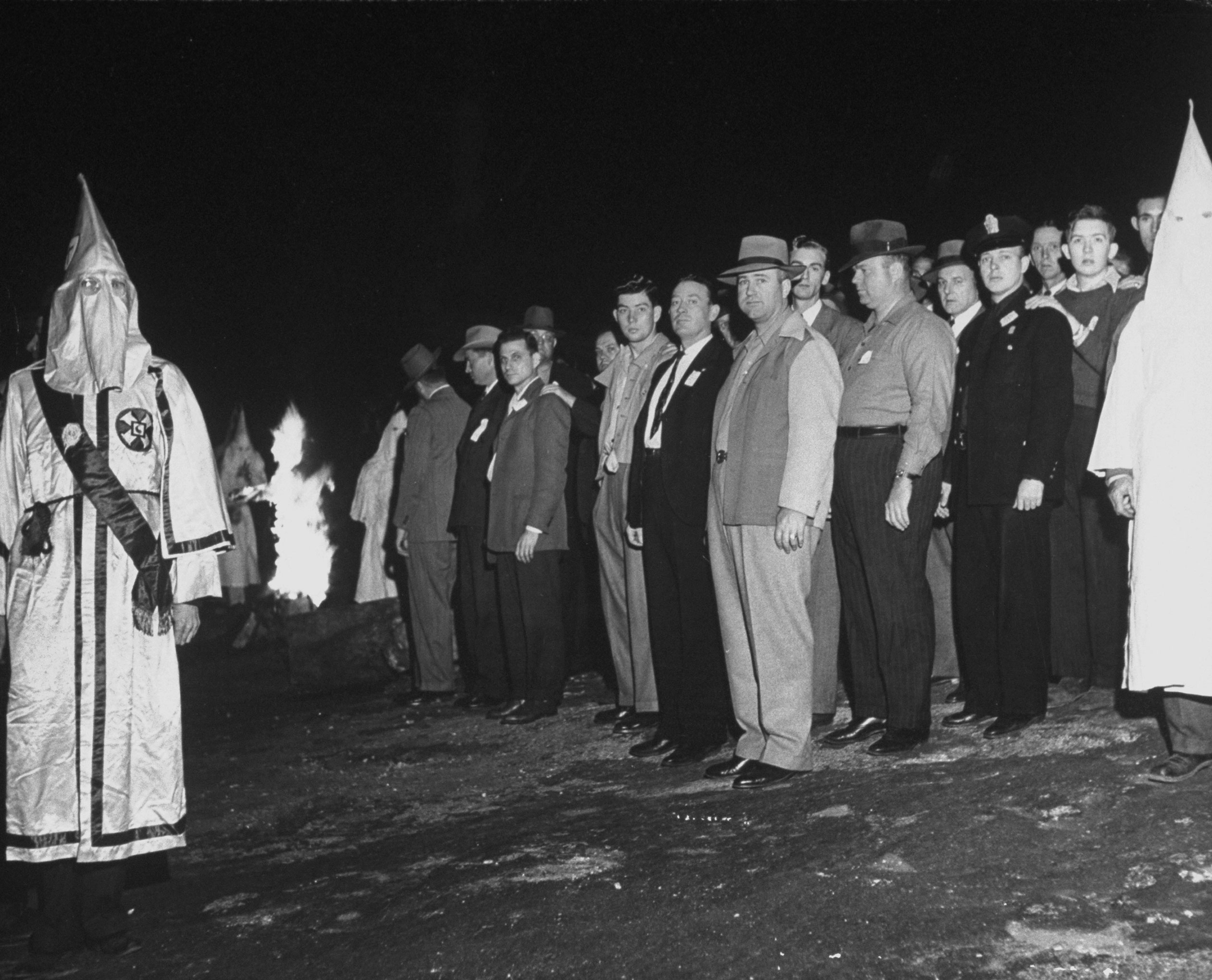 Klan initiates (including some Atlanta policemen) stand before a burning cross during a ritual in Georgia, 1946.