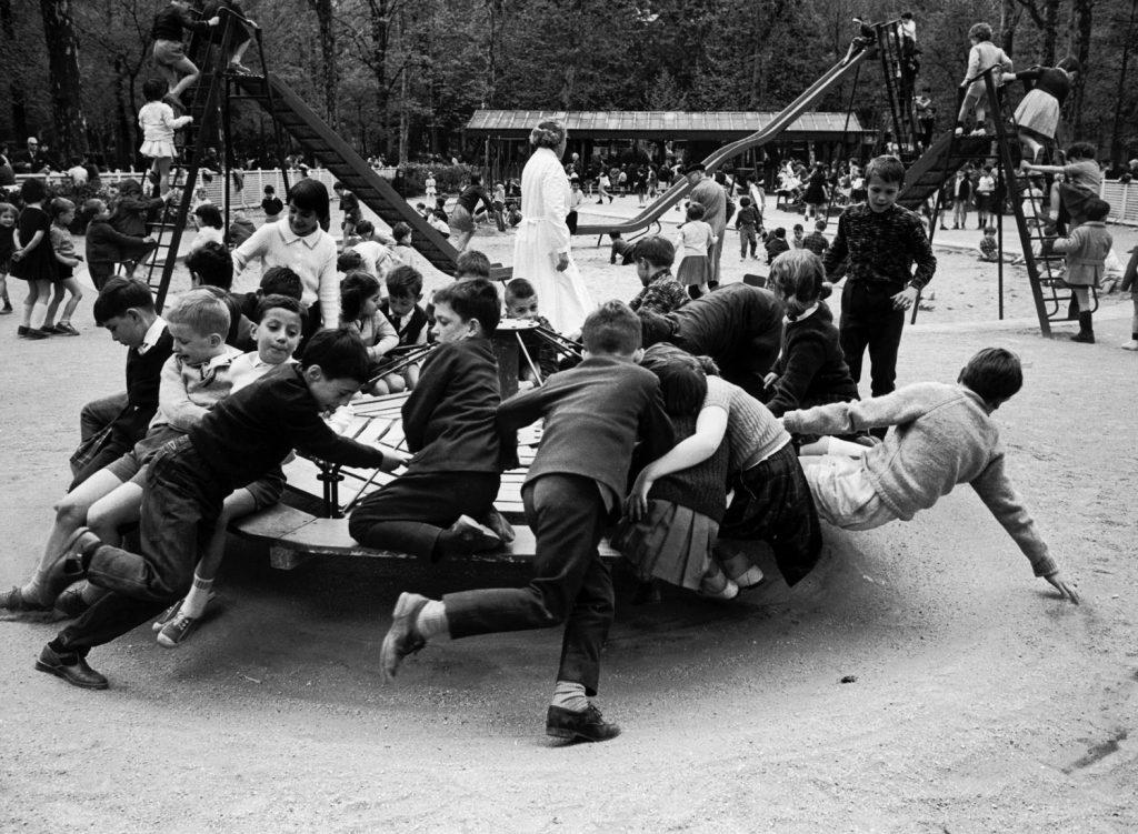 Parisian children riding merry-go-round in a playground, 1963.