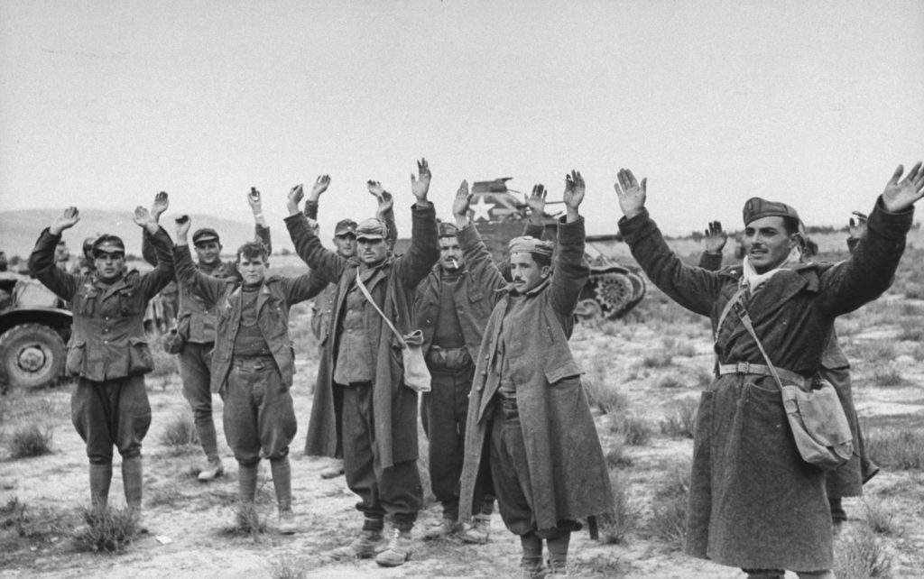 A group of Axis prisoners are taken during the Allied assault on German positions near Sened, Tunisia, 1943.