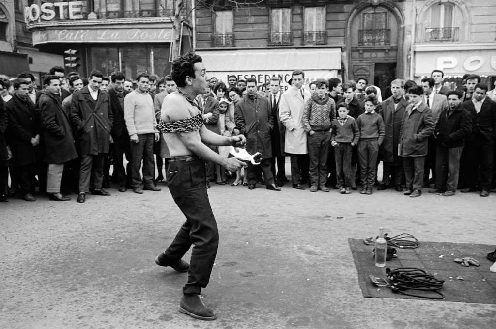 Street performer drawing a crowd, Paris, 1963.