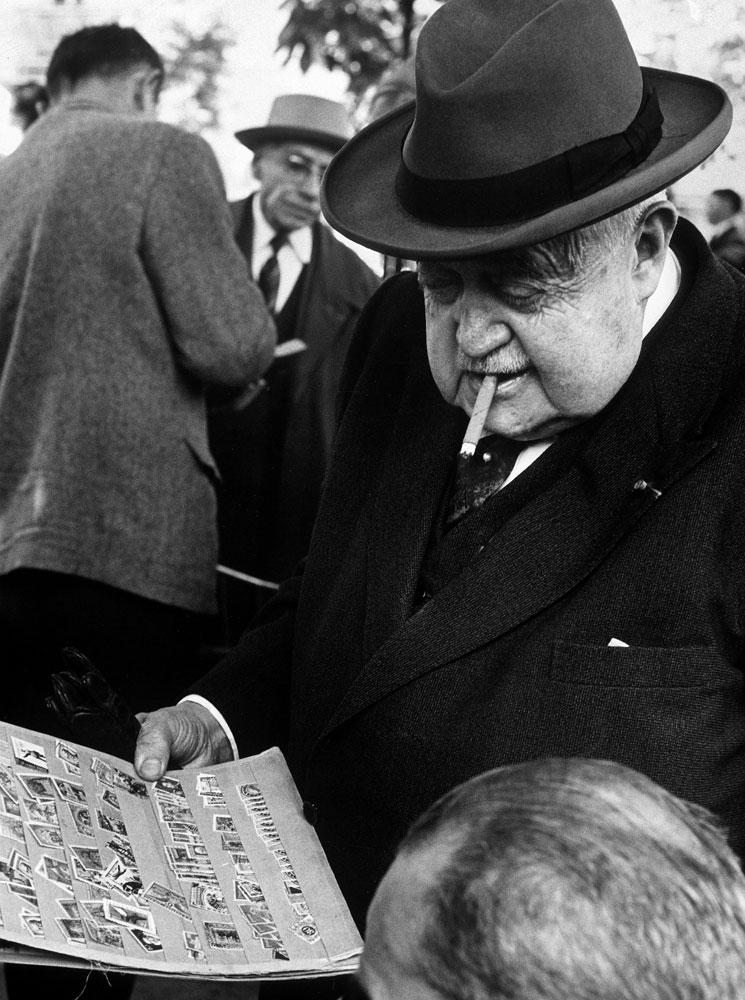 Man smoking cigar while examining stamps at stamp market on Avenue Matignon, Paris, 1963.