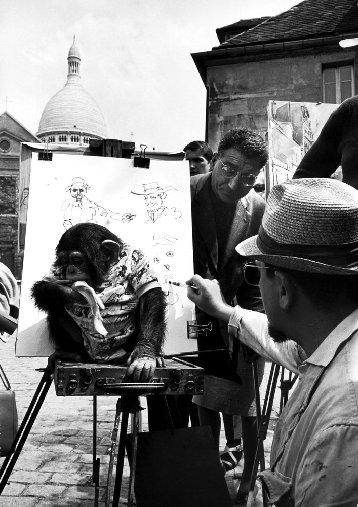Montmartre sidewalk artist and monkey entertaining tourists in the Place du Terte near Sacre Coeur, 1963.