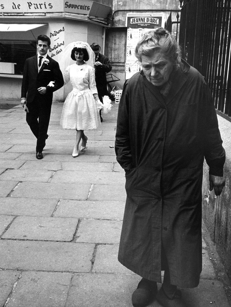 Elderly woman walking along street while bride and groom walk behind, Paris, 1963.