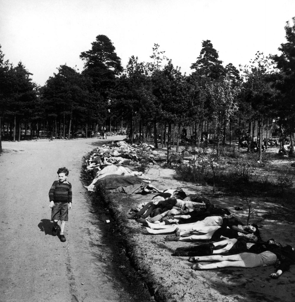 A small boy strolls down a road lined with dead bodies near the Bergen-Belsen concentration camp, 1945.