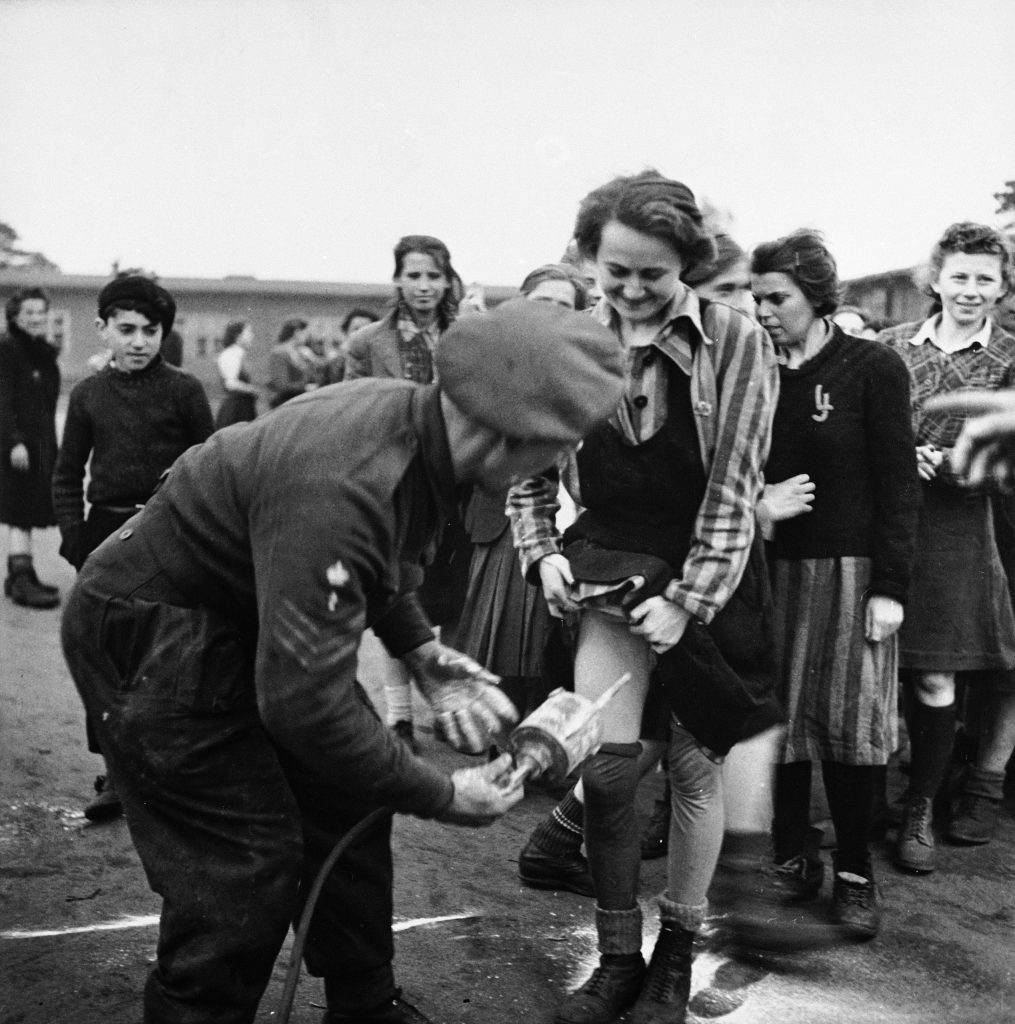 A British doctor administers delousing treatment of DDT up the skirt of an embarrassed-looking female prisoner at Bergen-Belsen, 1945.