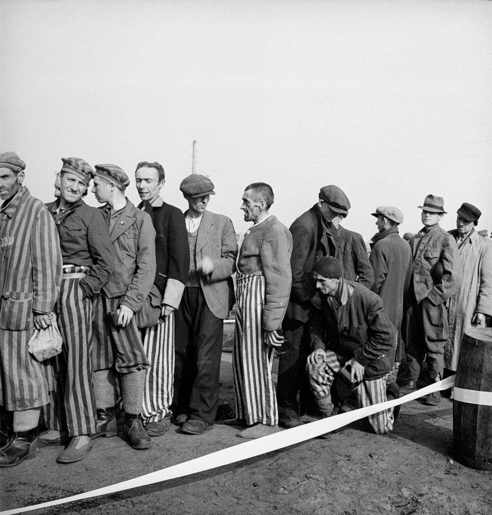 Newly liberated prisoners wait on line for food at Bergen-Belsen, 1945.