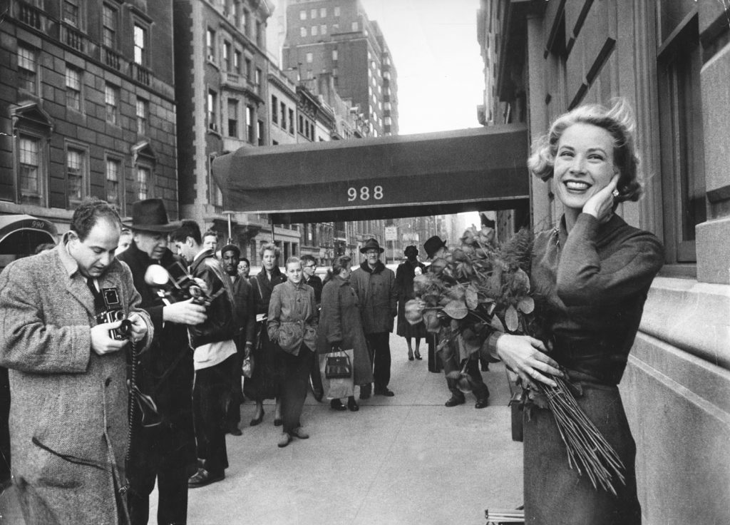Smiling in a brisk March wind and surrounded by photographers and fans, Grace Kelly poses just off of Fifth Avenue in New York, 1956.