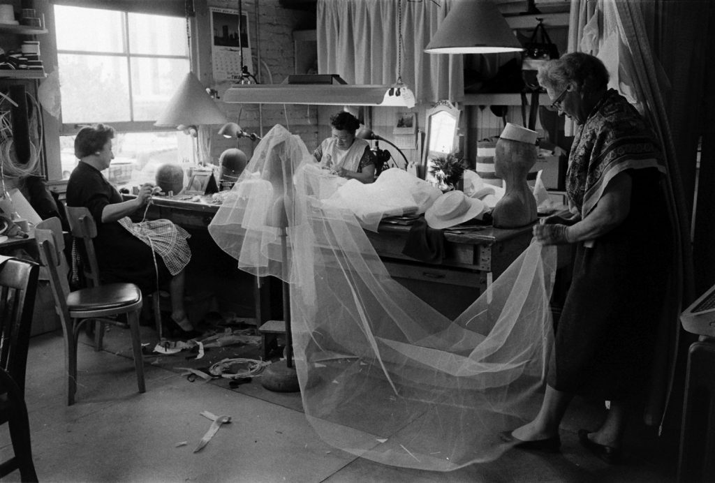 Seamstresses work on Grace Kelly's wedding dress and veil, conceived by MGM's wardrobe designer, Helen Rose, Hollywood, Calif., 1956.