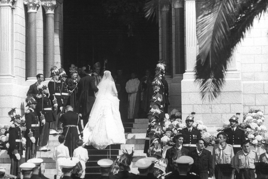 Prince Rainier III and Grace Kelly ascend the steps of Monaco Palace. Kelly's dress required 25 yards of silk taffeta, 100 yards of silk net, 125-year-old rose-point lace bought from a museum, and thousands of tiny pearls.