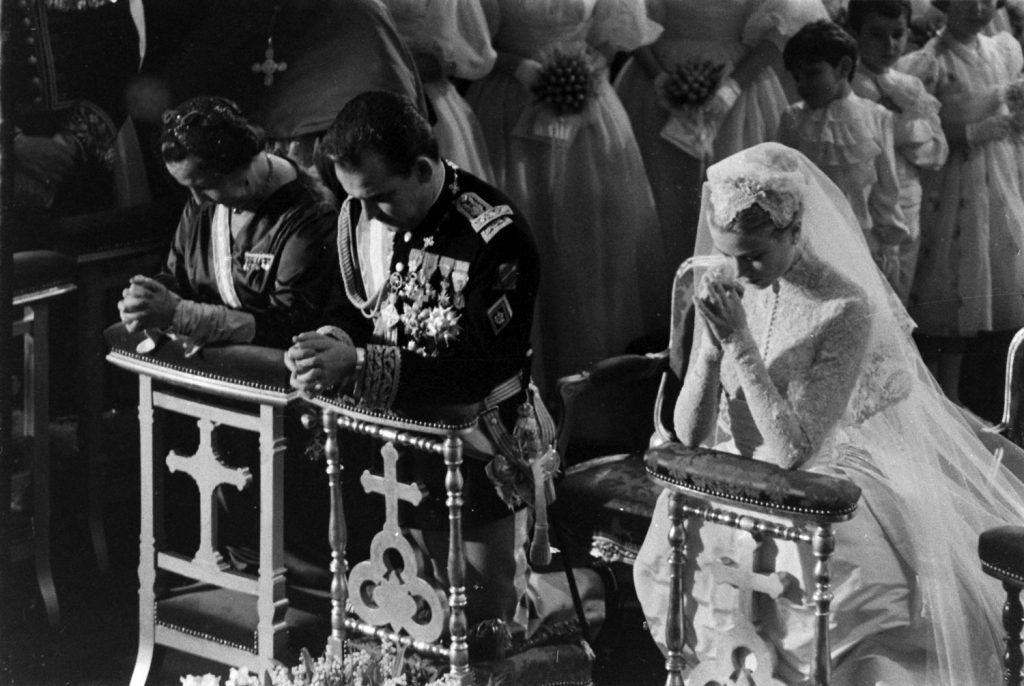 Grace Kelly and Prince Rainier kneel during Mass at their religious wedding, April 1956.